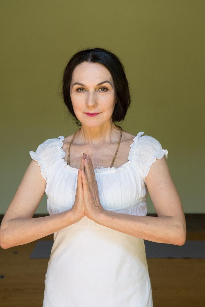 Sharon white dress studio portrait namaste #1. Photo by Derek Pashupa Goodwin.