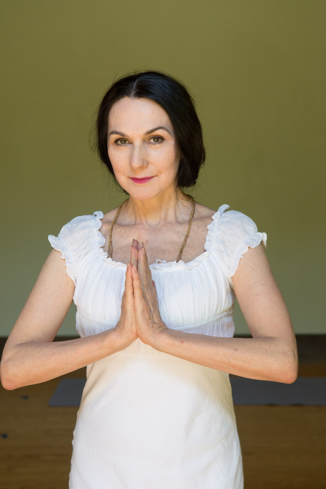 Sharon white dress studio portrait namaste #2. Photo by Derek Pashupa Goodwin.