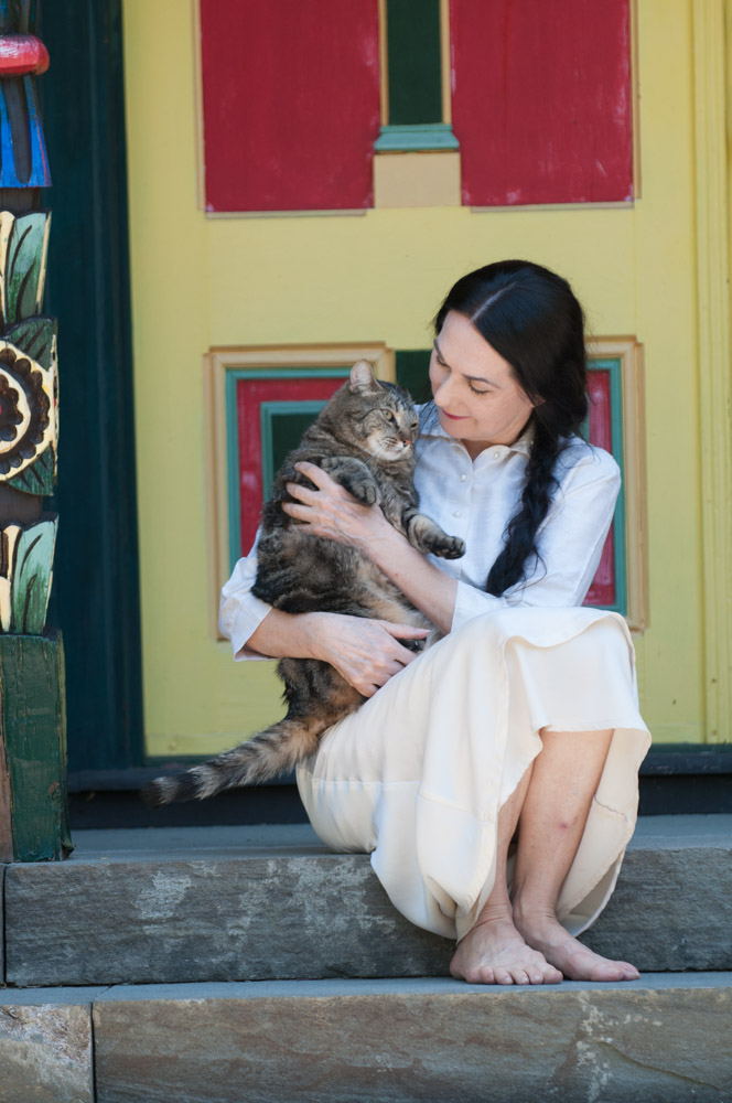 Sharon sitting on the front porch of Wild Woodstock home with Stripey Boy the cat #1. Photo by Derek Pashupa Goodwin.