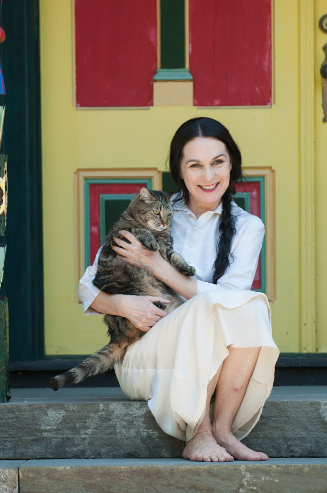 Sharon sitting on the front porch of Wild Woodstock home with Stripey Boy the cat #2. Photo by Derek Pashupa Goodwin.