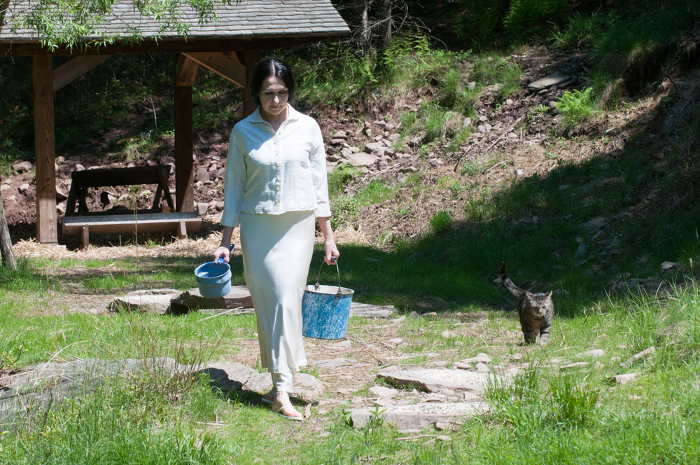 Sharon and Stripey Boy the cat putting food out for the deer at Wild Woodstock Forest Sanctuary. Photo by Derek Pashupa Goodwin.
