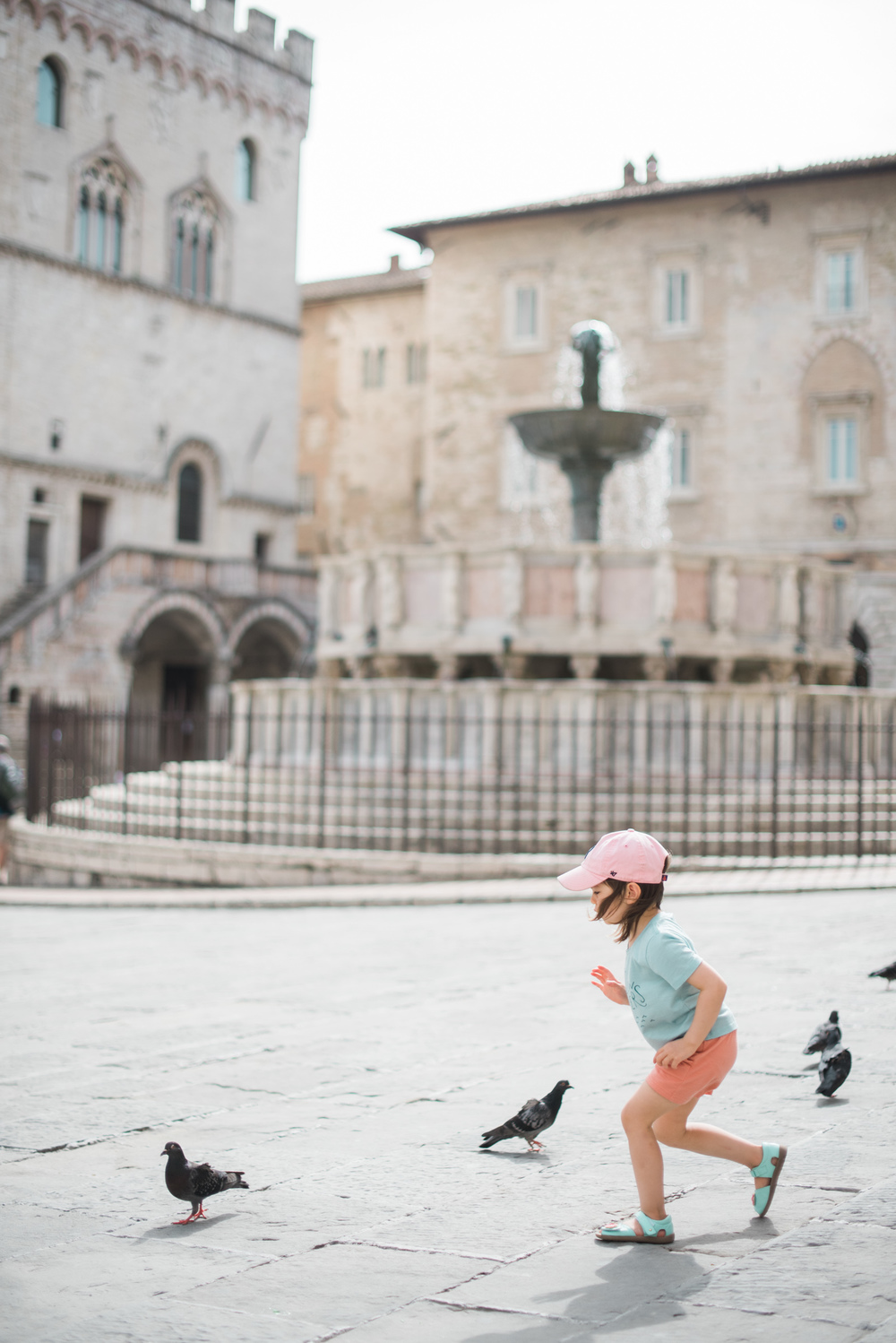Our little girl, clad in merino and exploring an Italian plaza.