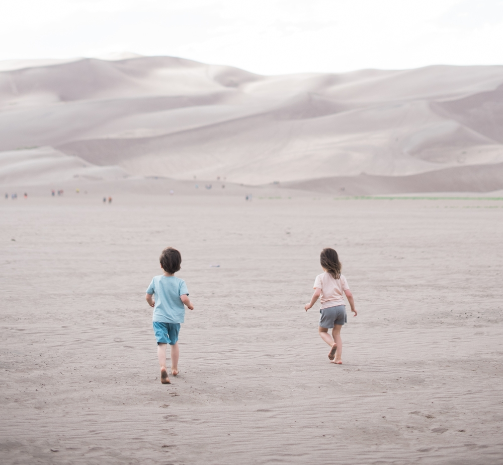 Our kids running to the Sand Dunes // pictured wearing our  merino tees  and  shorts .