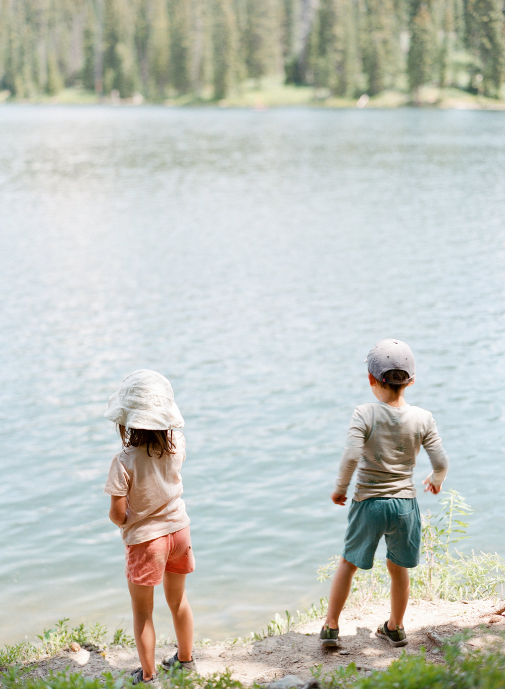 Our kids looking out upon a mountain lake after a night out camping. // Pictured wearing merino shorts, tee, and long john top.