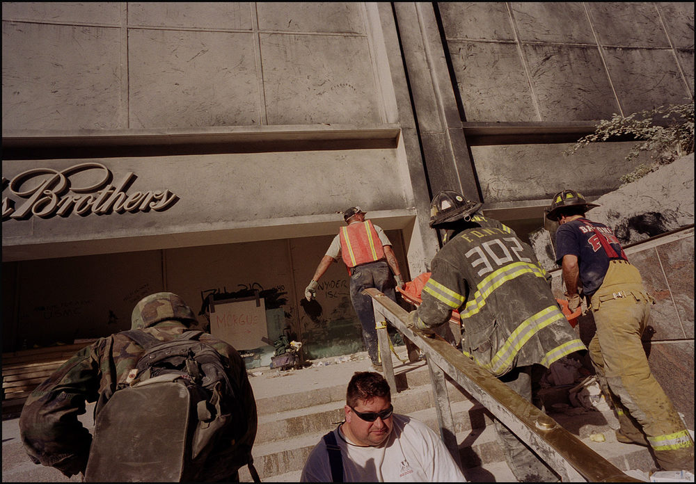 An army of rescue personnel carried bodies to a makeshift morgue past a message written in the dust— an eye for an eye.