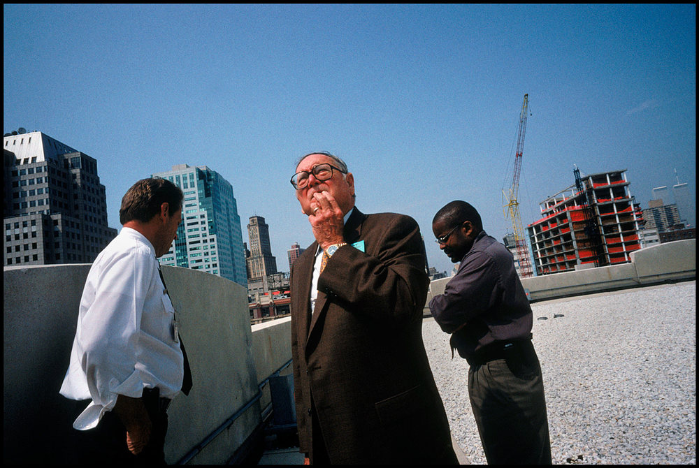 The twin towers standing behind him, Bill Patrick, former head of the U.S. Biological Weapons Program, surveys a New York City building for weakness to attack.