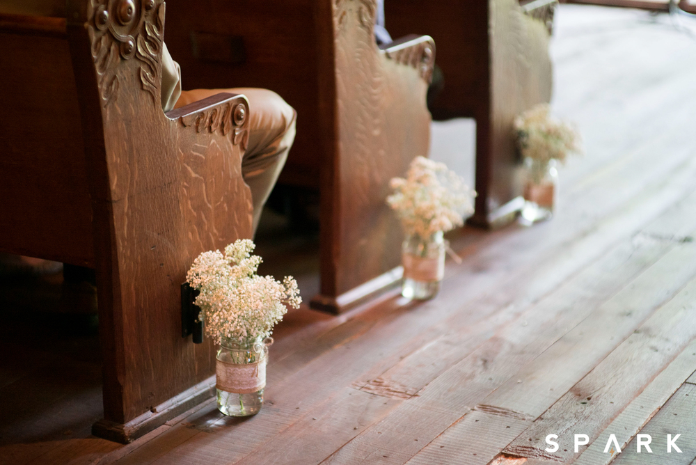 Pictured Above : Mason jars filled with baby's breath accented the pews of the Hope Wilderness Chapel at Dogwood Canyon.