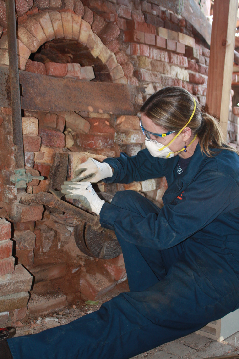 Claudia Chemello cleans iron elements in Kiln 7 to stabilize deterioration.