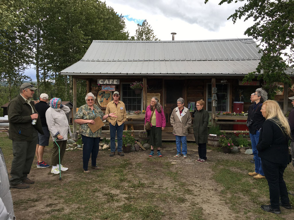"""Lois Walker (center left), longtime North Fork resident and North Fork historian gave some history on Polebridge starting at the Northern Lights Saloon. After the establishment of Glacier National Park in 1910 and the construction of a bridge across the North Fork of the Flathead River soon after, travel patterns changed. So William """"Bill"""" Adair and his wife moved to the present location in 1912. They built a cabin (the present-day Northern Lights Saloon) as their home on a 160-acre homestead and began construction of a store. The Adair Mercantile opened in 1914."""