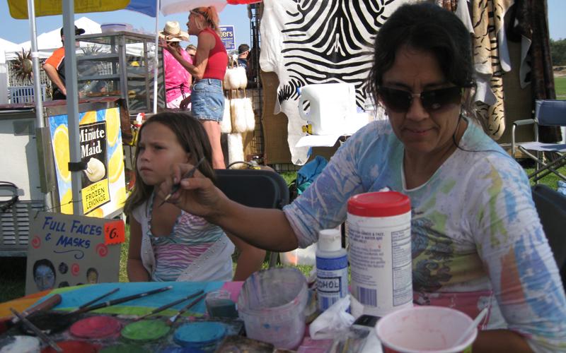 Melissa face painting at an art fair
