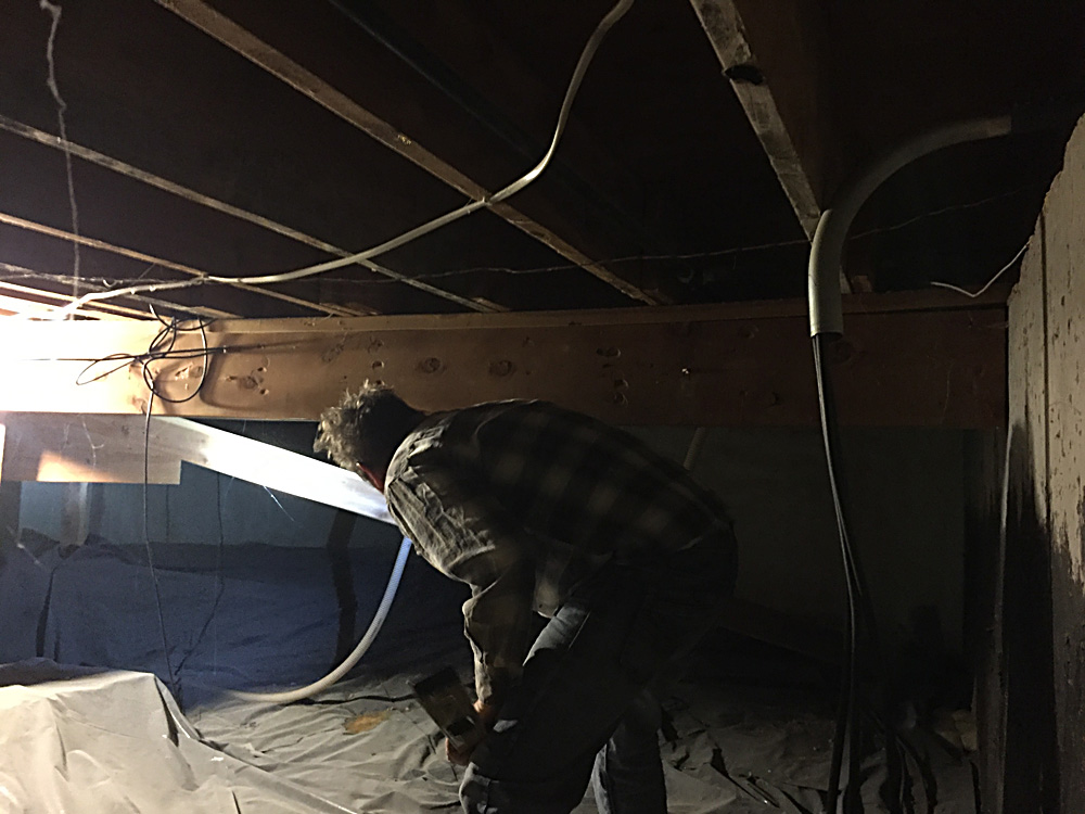 This is a terrible photo, but this this Tom in the crawl space under the office inspecting the structure to see why the office floor bowed. There are plenty of settling issues in this house and we ended up using a jack to shore up this beam.