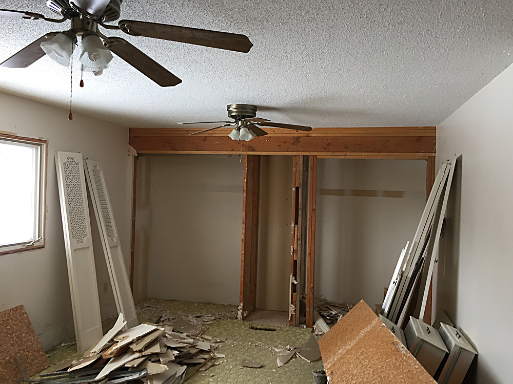 We had not one, but TWO ugly, dusty, rattly ceiling fans in this room! This pictures shows the closets coming down.