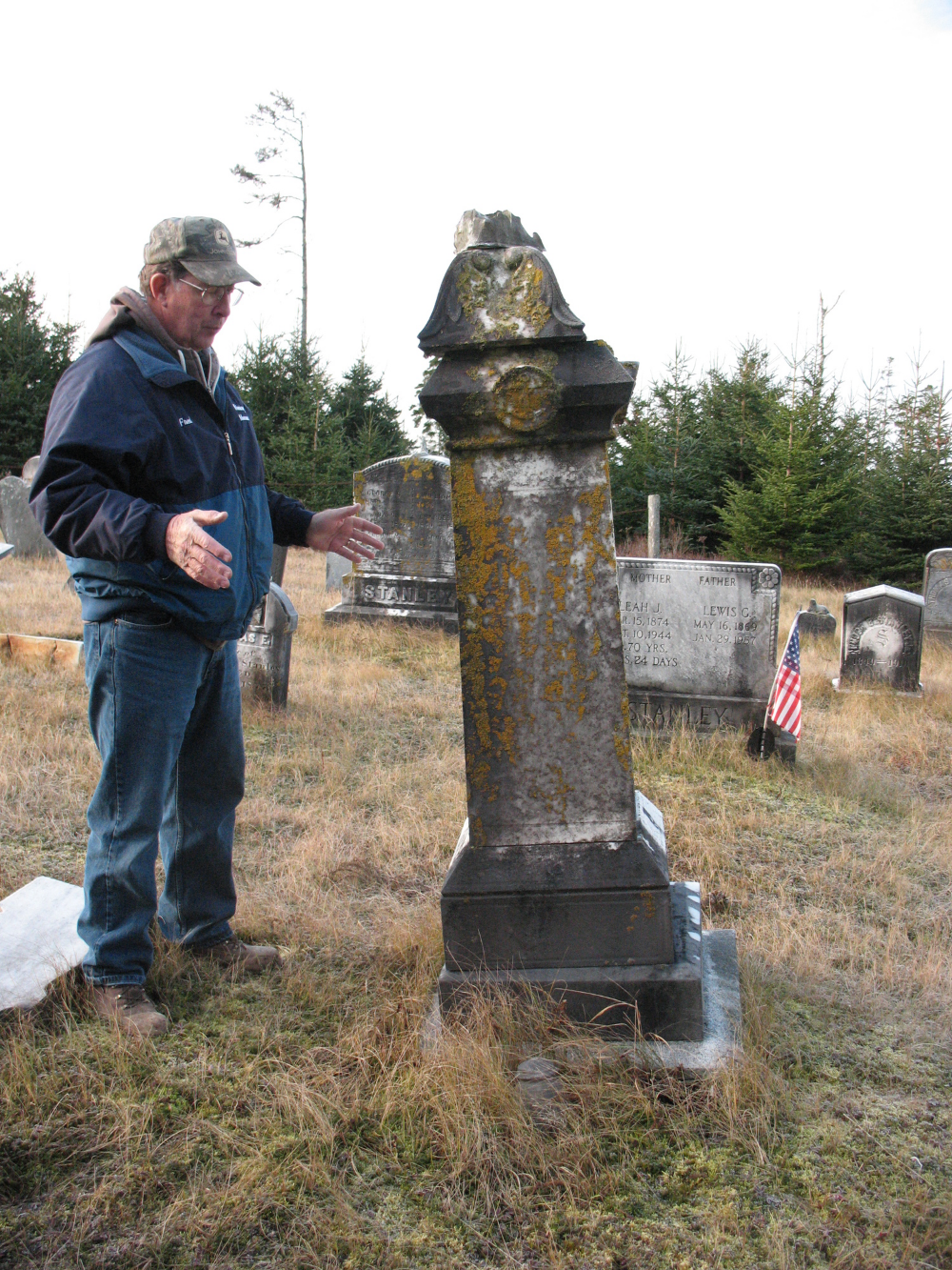 Fred Wieninger examines the leaning, broken Meltiah Richardson 1901 monument. Note the broken top-piece lying in the grass by the base.
