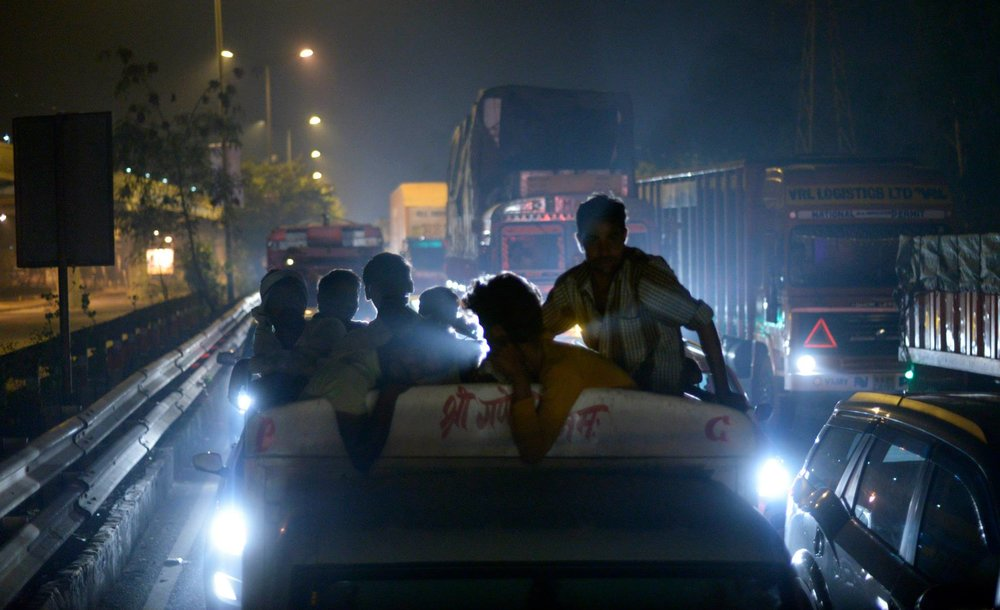 Taken from the back window of a bus making its way through midnight traffic in New Delhi.
