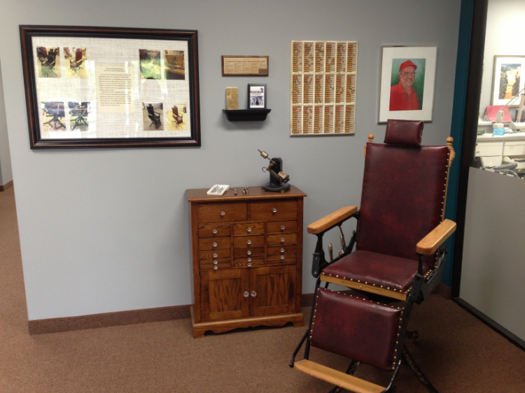 Our front entryway display including: reconstructed chair, a painting of Robert Renstrom, an abicus used for scheduling, the news article and brass bar, and a few pieces of old dental equipment placed on an old dental cabinet.