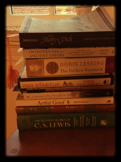 """My """"upstairs"""" stack of reading on my bedside table."""