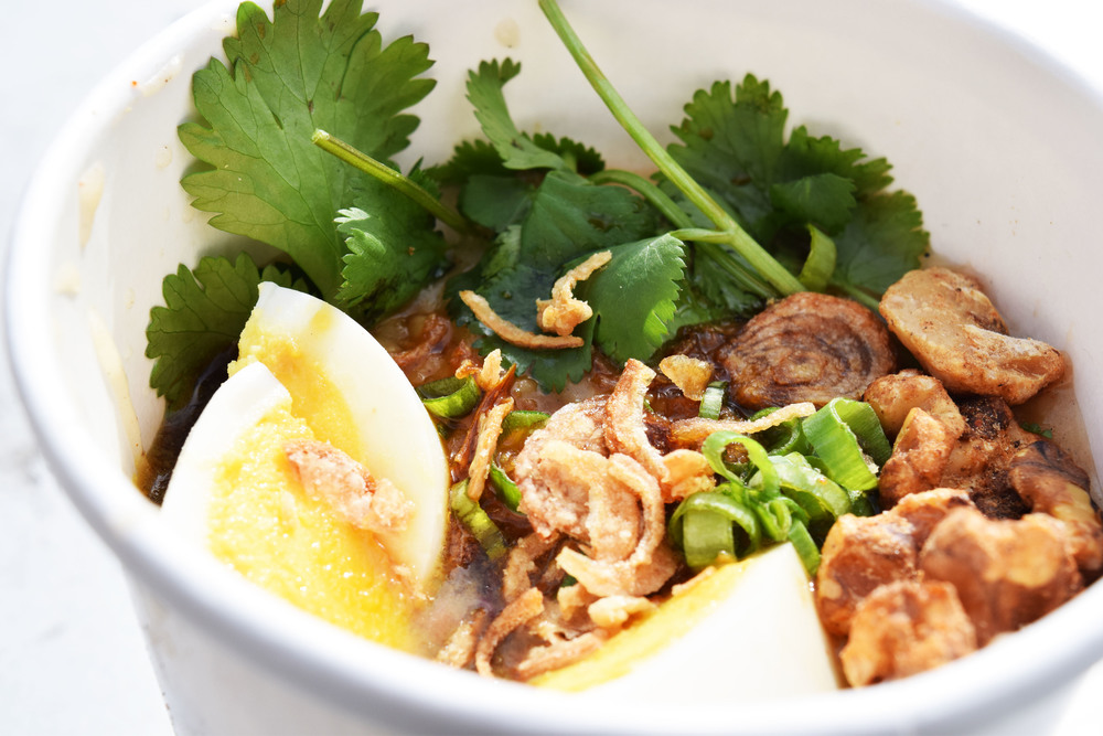CHICKEN & EGG CONGEE hard boiled egg, cilantro, spiced walnuts, scallion, soy drizzle, onion oil in daily broth