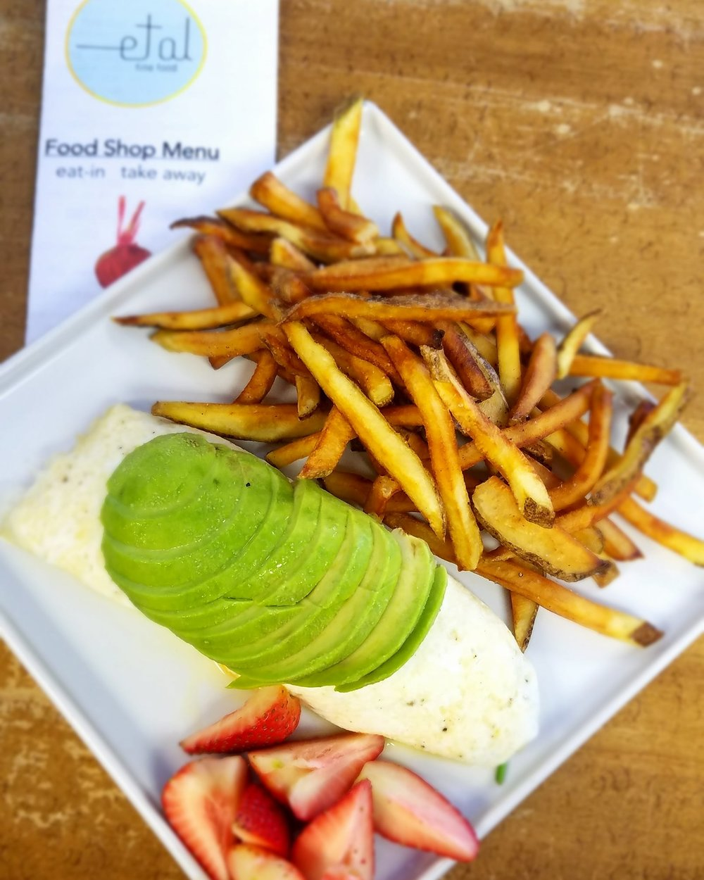 Egg white, spinach and cheese omelet with sliced avocado on top and a side of fresh fruit and hand cut french fries.