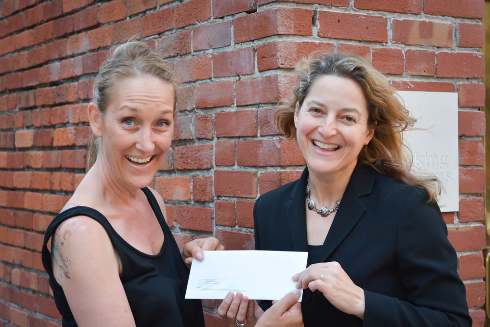 Kimberli of Fairyella Ice Pops receives her grant check from Working Solutions' Laura Hoover Photo by Luke George Photography