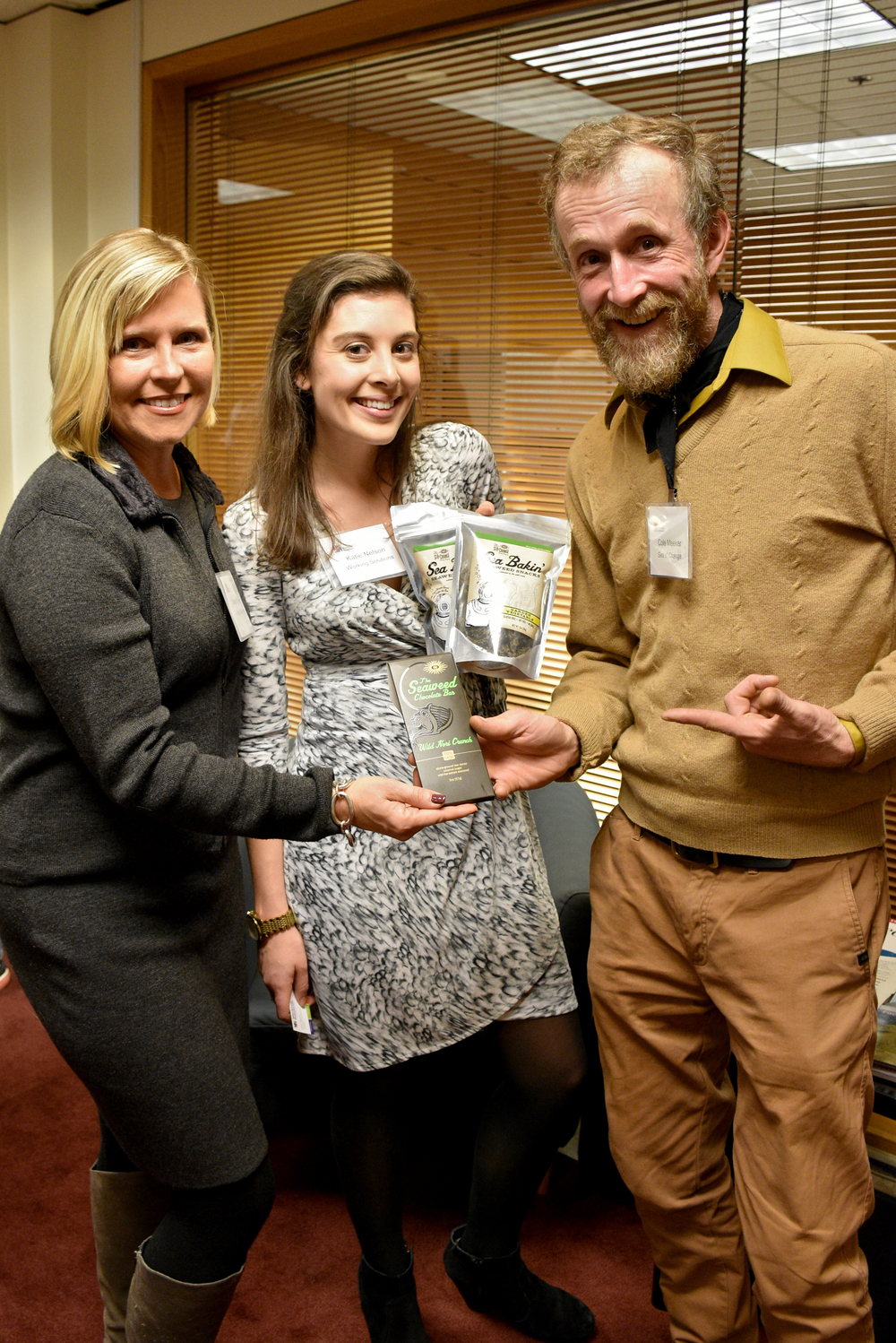 Cole Meeker of Sea of Change Trading Company shows off his seaweed snacks and seaweed chocolate bar to Working Solutions Director of Business Development Laurie O'Hara and Marketing & Development Associate Katie Nelson