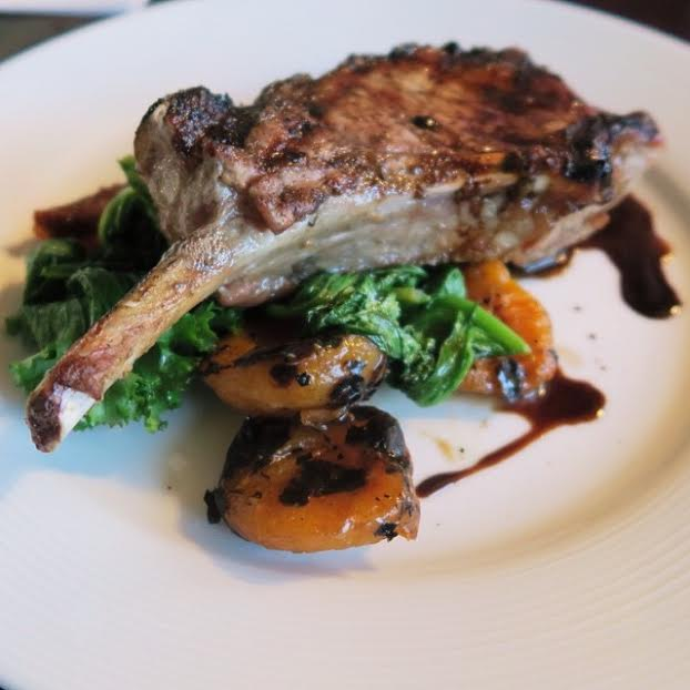 Grilled Kurobuta Porkchop served with mustard greens, grilled apricots, and date purée, vincotto.