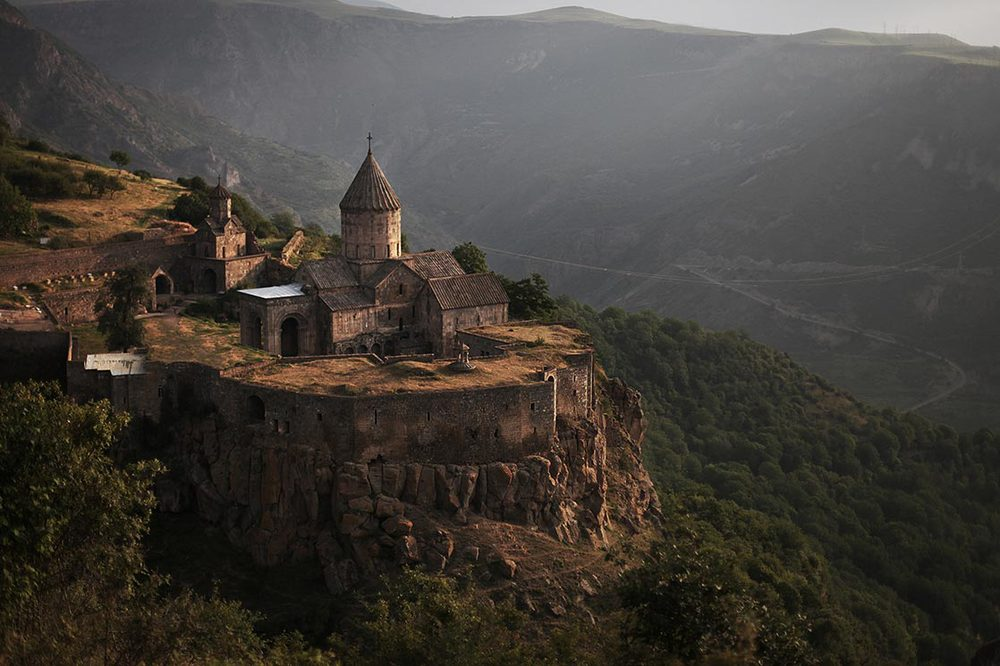 "Tatev   is a 9th-century monastery located on a large basalt plateau   in southeastern of Armenia  . The term ""Tatev"" usually refers to the monastery. The monastic ensemble stands on the edge of a deep gorge of the Vorotan River"