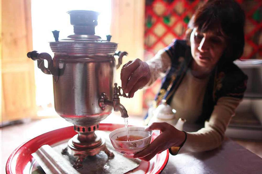 The woman in the yurt uses a Samovar to boil water, which is typically used to make tea in Central Asia and Russia   | KYRGYZSTAN