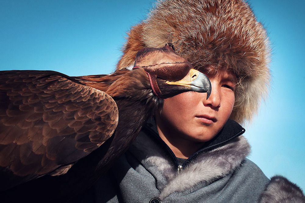 A young Kazakh falconer. His eagle's eyes are covered by a tomoro, a leather mask intended to keep it from feeling stressed or recklessly attacking anyone /  Jeune aiglier kazakh. Son rapace a les yeux recouverts d'un  tomoro , un masque en cuir pour l'empêcher de stresser et d'attaquer sans discernemen  | KAZAKHSTAN