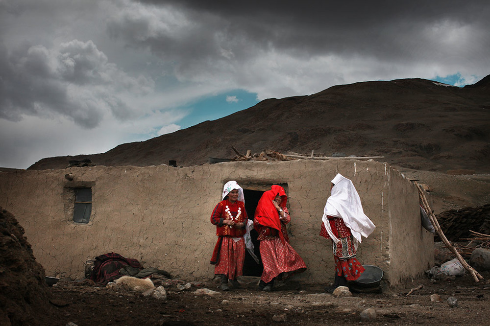 In the villages of Wakhan Corridor, families perform unchanging rituals. The women with their heads covered in white are married, the ones in red aren't /  Dans les villages du corridor du Wakhan, les familles s'organisent autour de rites immuables. Les femmes couvertes de voiles blancs sont mariées, celles en rouge ne le sont pas  | AFGHANISTAN