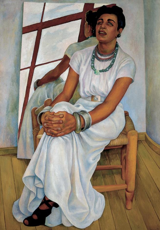 Diego Rivera   Retrato de Lupe Marín , 1938  Óleo sobre tela  171.3 x 122.3  Uno de los géneros que Diego Rivera desarrolló en el caballete, fue el del retrato. En éste, el muralista experimentó una perspectiva alterna a la clásica. Esta obra se vale de las referencias corporales de Lupe Marín, a partir de su altura, el color de los ojos y lo expresivo de sus manos. En la obra, Rivera presentó un espejo como un elemento que le permitió abrir las posibilidades de la composición con base en el reflejo del personaje, obteniendo la ruptura espacio temporal de la imagen.