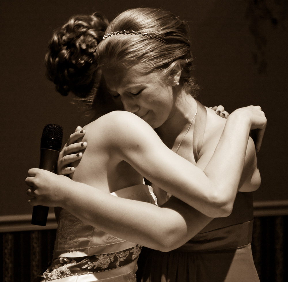 Photograph of a bride and maid of honor hugging
