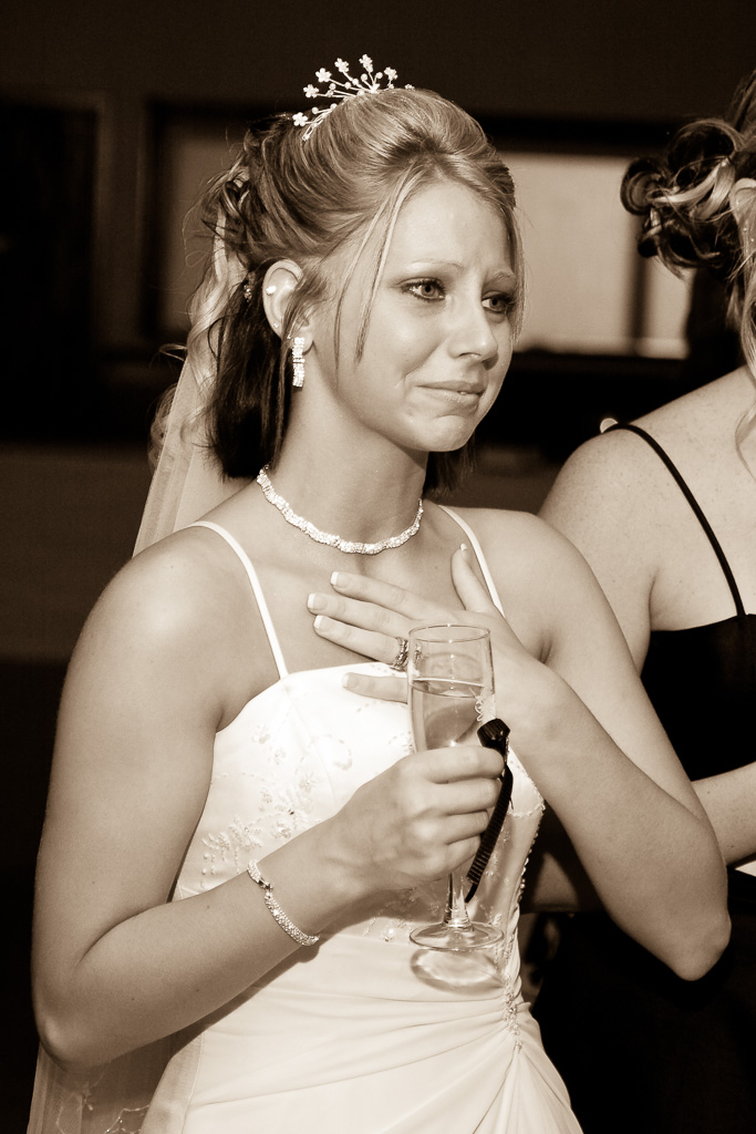Candid sepia photograph of a bride during toast