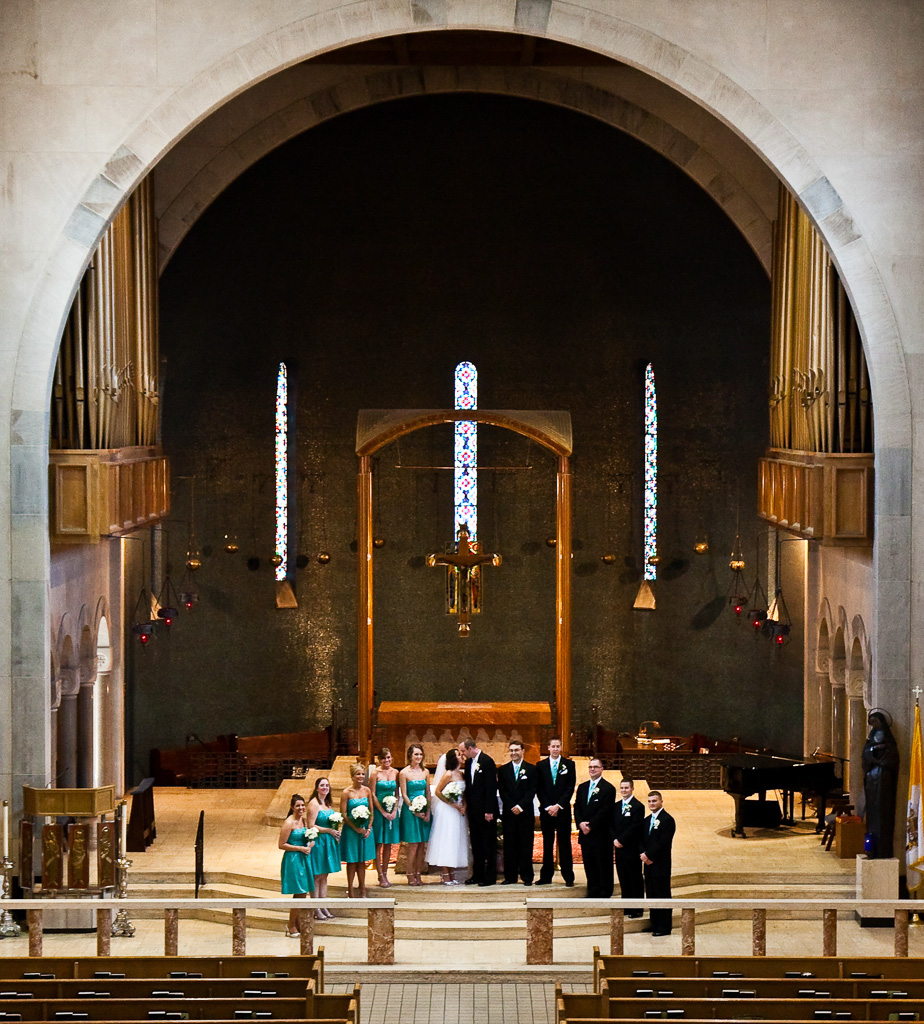 Formal photograph of bride and groom with wedding party in church