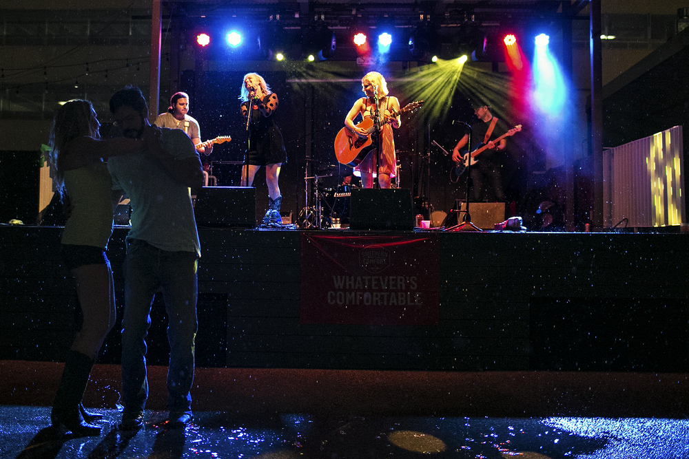 A couple dances under the rain to the music of The Rankin Twins during an iHeartRadio-sponsored show at The Belmont in Austin, Texas on July 15, 2014.
