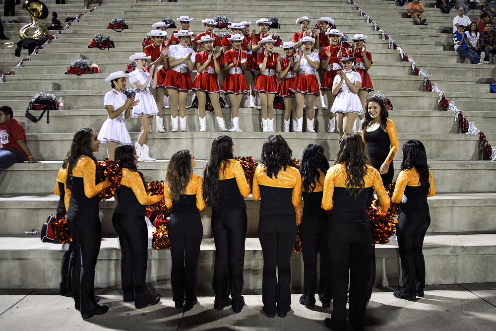 Jefferson Silva High School's drill team (top) is visited by the home team's dance team during fourth quarter action of the Jefferson vs El Paso high school football game played on September 19, 2014 at R. R. Jones Stadium in El Paso, Texas. A sportsmanship and hospitality gesture, spirit squads for the home team visit their counterparts in the visitor stands, with the senior captains for both teams introducing their members and then taking photos together.