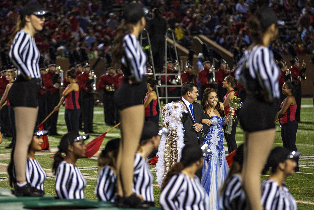 Katy High School's homecoming court is presented during halftime of the Tigers' homecoming game against the Katy Taylor Mustangs played on September 26, 2014 at Jack Rhodes Memorial Stadium in Katy, Texas. While homecoming is practiced all throughout the United States, Texas high schools are unique in their use of large homecoming mums and garters for girls and boys, respectively. While tradition originally called for a boy to present his homecoming dance date with a single chrysanthemum, hence the name mums, the gesture has grown larger and more elaborate as the decades go by. The girl in turn will give her date a matching, but smaller, garter to be worn in his upper arm.