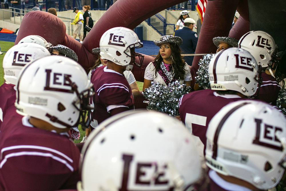 "Members of Midland Lee High School's drill Team, ""The Dixie Dolls,"" watch as the Rebels head back to the locker room after warming up prior to their rivalry game against Odessa Permian on Oct. 12, 2014 at Grande Communications Stadium in Midland, Texas. Although both schools are far removed from their heyday as perennial state contenders, the annual game still draws over ten thousand attendees every year and is the most important game in both teams' schedules."