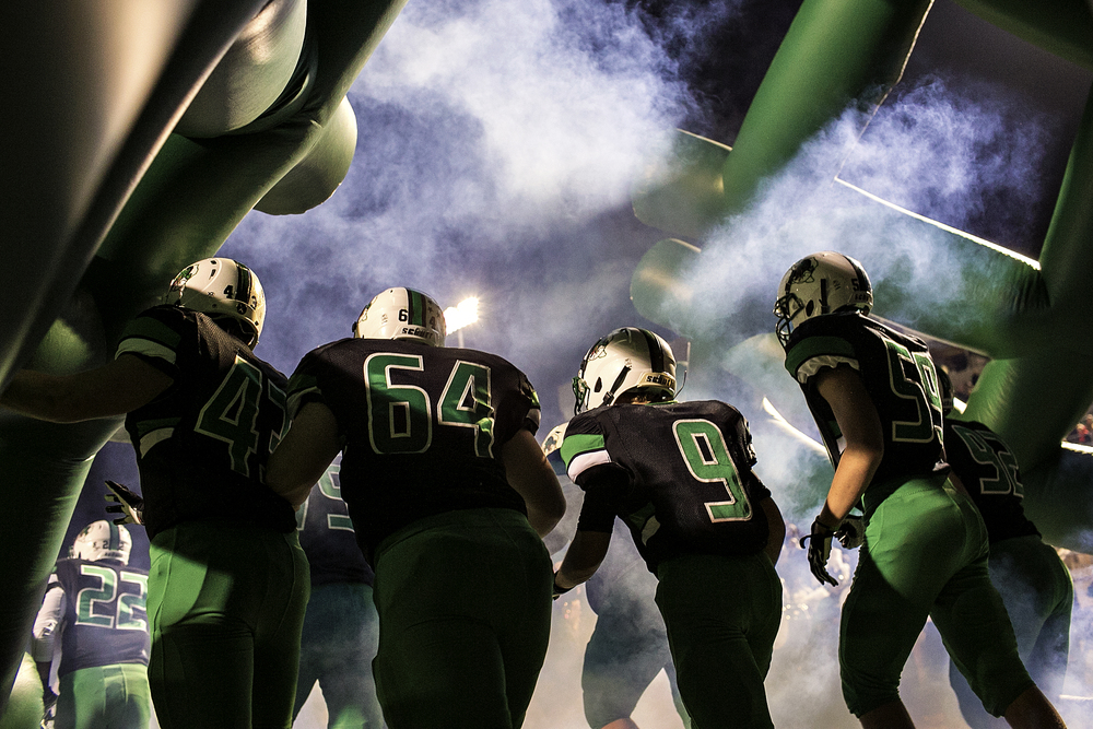 Southlake Carroll players Steven Stewart (43), Grant Stewart (64), Connor Lanham (9) and John Miscoll (59) run out of the tunnel prior to the second half of the Dragons' senior night game against Haltom on Oct. 31, 2014 at Dragon Stadium in Southlake, Texas. Southlake Carroll handily beat Haltom 62-0. The Carroll Dragons are one of the most successful programs in Texas high school football, having won eight state championships, which ties them with Celina High School for most in state history.