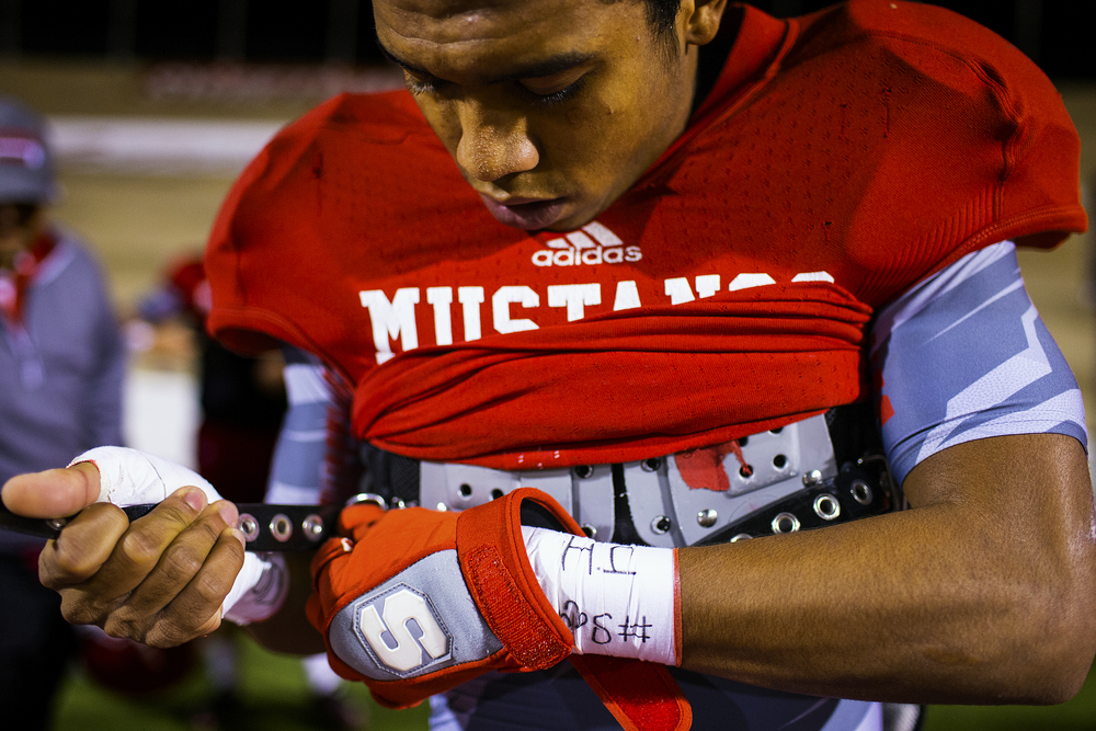 Senior Sweetwater wide receiver Isaiah Mcgee (5) tightens up his pads prior to the Mustangs' senior night game against the Lamesa Golden Tornadoes Nov. 7, 2014 at the Mustang Bowl in Sweetwater, Texas. The Mustangs are a proud program which has suffered through rough years after a string of 22 playoff appearances in 25 years, with its last winning season coming in 2008. Attendance at the Bowl declined and facilities fell into disrepair, and it wasn't until the recent renovations and this year's 10-0 season by the Mustang that attendance numbers picked up.