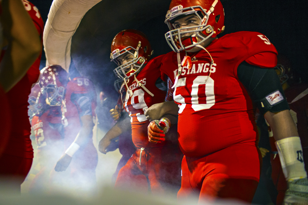 Carlos Gallegos (79) and Cory Mendez (50) walk out of the tunnel with their teammates before the second half kickoff of their senior night game against Lamesa on Nov. 7, 2014 at the Mustang Bowl in Sweetwater, Texas. The Mustangs wrapped up the regular season with a 57-6 win over the Golden Tornadoes, giving the program an undisputed district championship, an undefeated 10-win season and its first playoff berth since 2008.