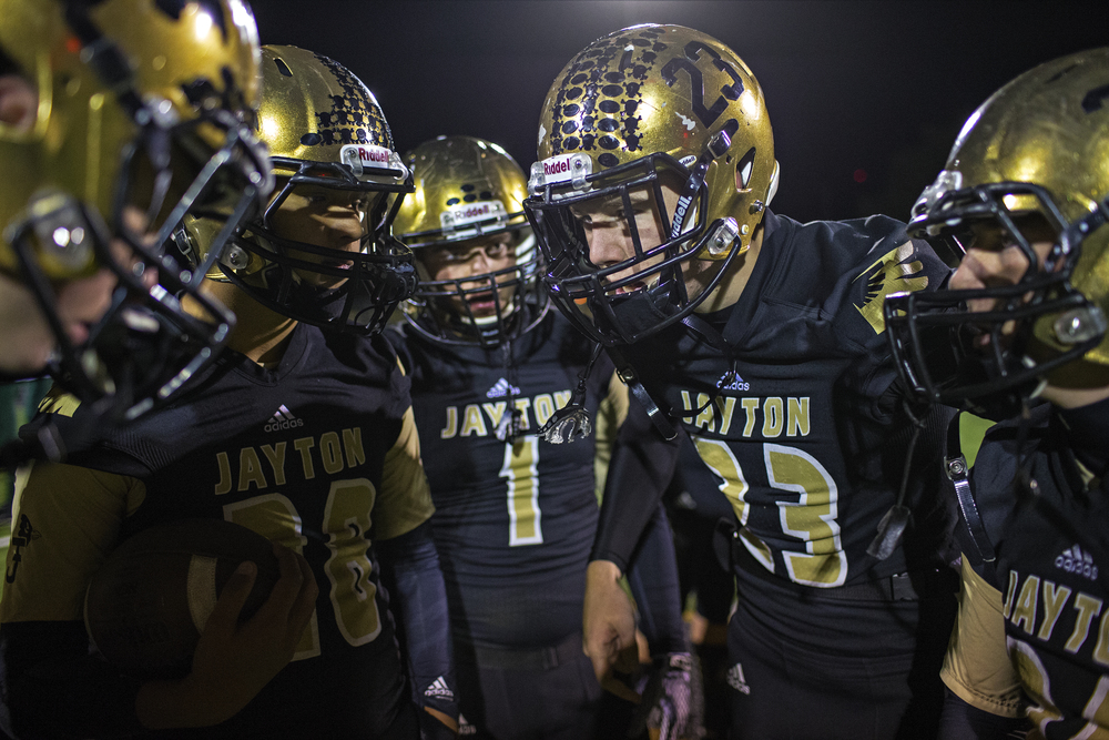 Jayton junior quarterback Slade Coulter speaks to his offense in the huddle as the Jaybirds warm up for their bi-district playoff game against Guthrie on Nov. 14, 2014 at Jaybird Stadium in Jayton, Texas. Six-man football was invented in Nebraska in 1934 and was sanctioned by the UIL in Texas four years later, with 55 schools competing that year. Today, there are around 130 public schools participating in UIL competition, along with over 50 private schools in other leagues.