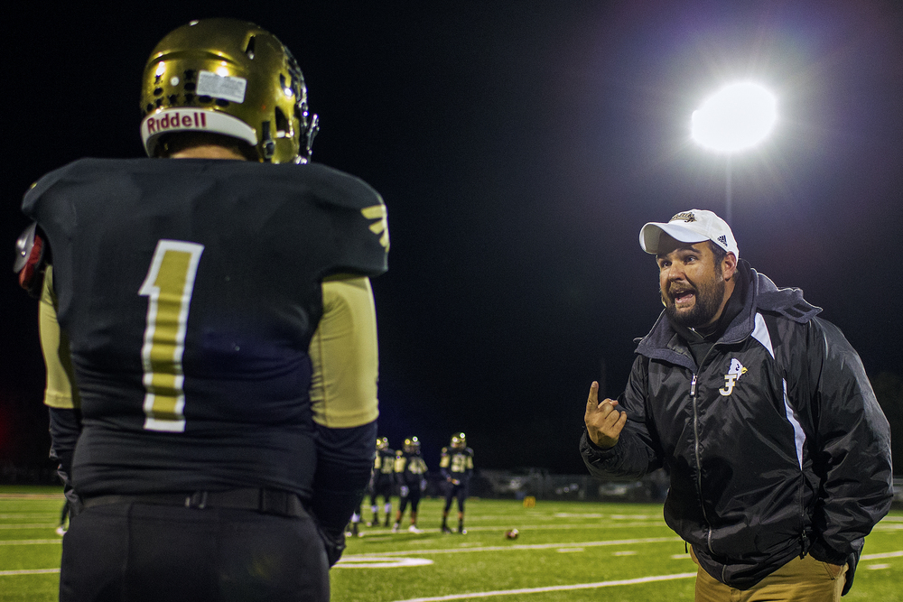 Jayton head coach Josh Stanaland talks to sophomore center/defensive end Kobe Lisenbee during the third quarter of the Jaybirds' bi-district playoff game against Guthrie on Nov. 14, 2014 at Jaybird Stadium in Jayton, Texas. Due to its limited number of players in the roster, six-man football requires most players to take positions on both sides of the ball, with many playing almost every snap of the game.