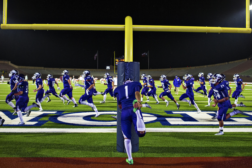 Weslaco kicker Edward Limas stretches on the field goal post as his teammates warm up in front of him before second half action of the Panthers' area playoff game against Laredo United on Nov. 22, 2014 at Alamo Stadium in San Antonio, Texas. Limas and the Panthers tried furiously to keep up with the Longhorns high-powered passing attack, but were unable to match United's offensive production and lost 40-28. Laredo United will now face their biggest test yet in San Antonio-area powerhouse Converse Judson.