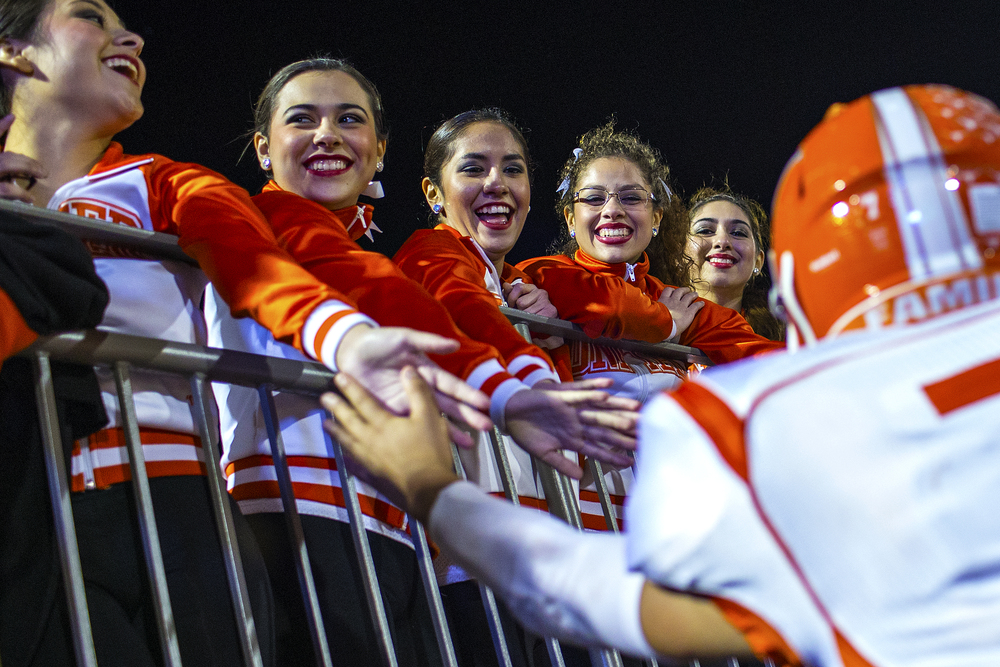 Laredo United drill team members celebrate with wide receiver Derek Luna and his teammates after the Longhorns defeated Weslaco 40-28 on Nov. 22, 2014 at Alamo Stadium in San Antonio, Texas to advance to the third round of the Texas high school football playoffs, where they will face Converse Judson.