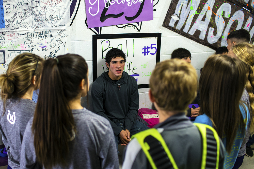 "Luis Castillo talks to classmates in a hallway at Mason High School while he kills time before the first practice of the day on Dec. 16, 2014 in Mason, Texas. Luis and Miguel's life is consumed by school and athletics. ""There's not much to do in Mason, so we try to stay busy with sports,"" says Luis. They have both excelled in the school's basketball, track, baseball and tennis teams, in addition to playing both ways in the football team. They have also each been awarded several places in both academic and athletic all-state teams throughout their career."