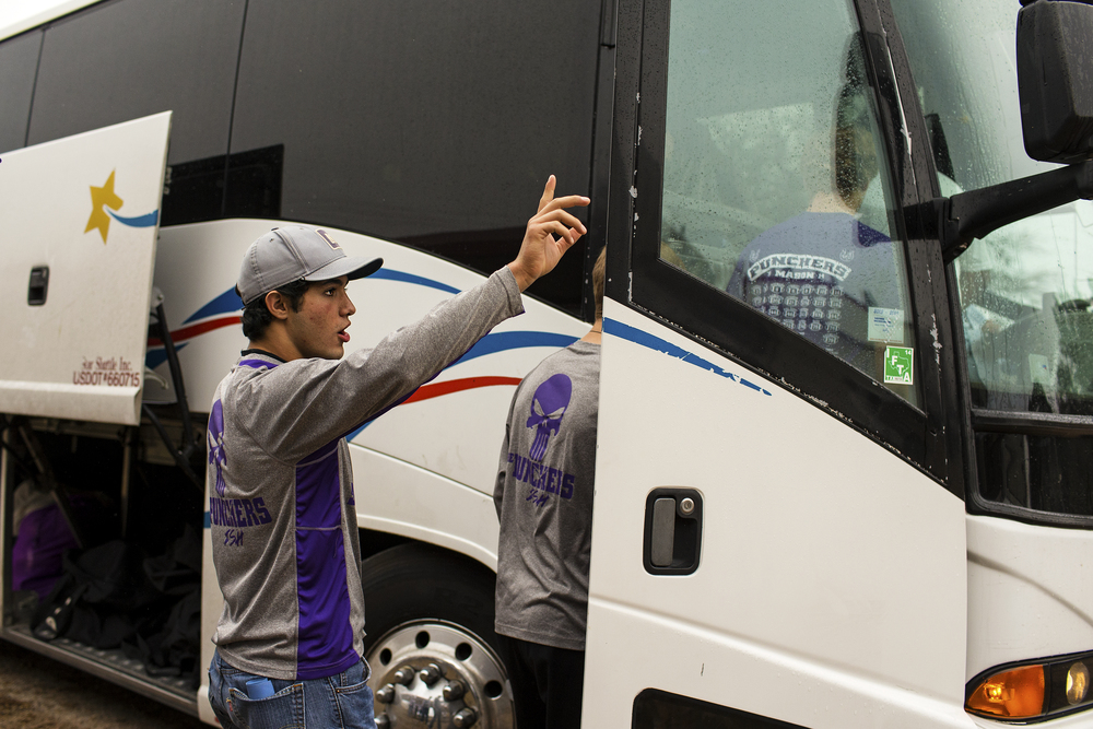 Luis Castillo waves to cheering fans as he boards the bus that will take the team to Fort Worth, where the Punchers will practice in TCU's campus later that day. A large number of fans were out in Mason's streets to wave and wish good luck to the team as they start their journey out of Mason, Texas on Dec. 17, 2014.