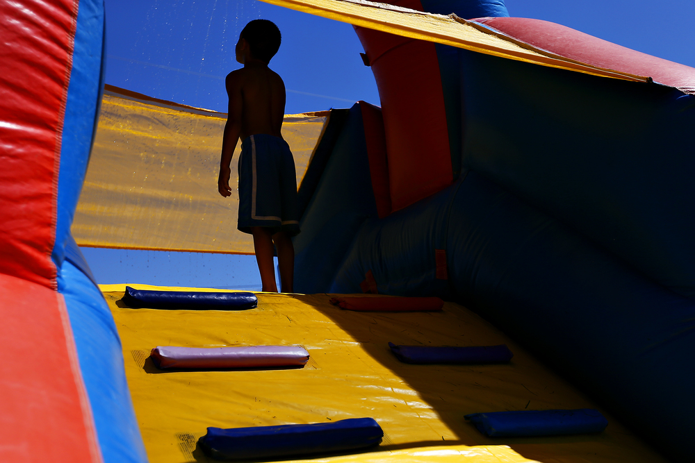 Aaden Barnett, 6, gets ready to go down a water slide during the 11th annual back-to-school bash at the John B. Hughes apartments in Springfield, Mo. on July 31, 2015. The bash, which is organized by the complex's compliance manager Sophia Smith, serves to give every kid living at the apartments a new backpack filled with school supplies for the coming year.