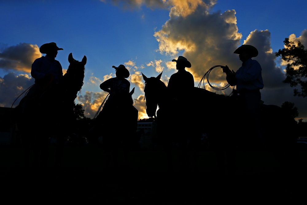 (from left) Jeff Schneider, Brye Crite and Springfield residents Wenten and Bryan Reiter talk before the start of the team roping event, where they will all compete, during the Carthage Stampede Championship Rodeo at the Carthage Saddle Club Arena in Carthage, Mo. on June 26, 2015.