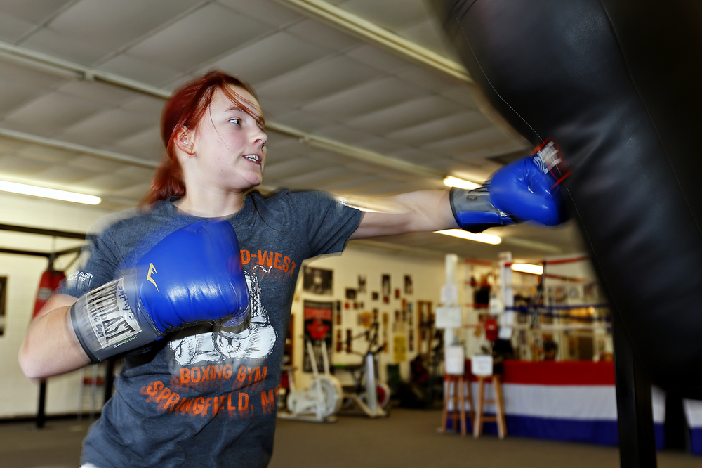 Shilyn Bradt, a 13-year-old who survived a severe gastrointestinal disease and multiple respiratory arrests at just weeks old, trains by boxing against a punching bag at Smitty's Midwest Boxing Gym in Springfield, Mo. on Feb. 4, 2016.