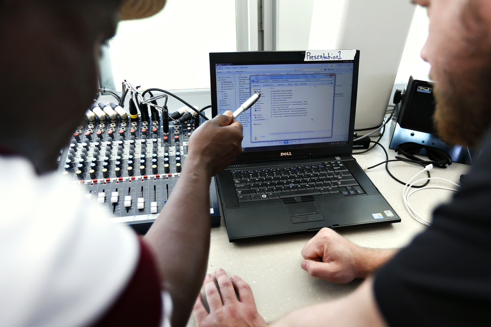 Missouri State Bears track & field head coach Ronald Boyce instructs athletic facilities production manager Matt Jones on which music tracks to play during the Missouri State Invitational track meet held at Betty and Bobby Allison South Stadium in Springfield, Mo. on April 22, 2016.